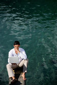 Businessman sat by water — Stock Photo