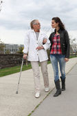 Young woman assisting a senior lady — Stock Photo