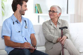 Senior woman talking to a young medic — Stock Photo