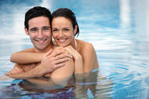Couple heureux hugging en une piscine — Photo