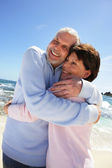 Older couple hugging on a beach — Stock Photo