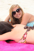 Young woman sunbathing at the beach with her friend — Stock Photo