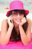 Girl in a shocking pink hat making a call on the beach — Stock Photo