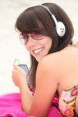 Girl listening to music on the beach — Stock Photo