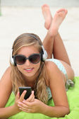 Young woman listening to music while tanning at the beach — Stock Photo