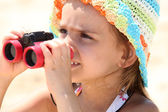 Little girl on the beach with binoculars — Stock Photo