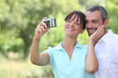 Couple in countryside taking photos — Stock Photo