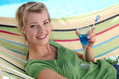 Woman in hammock drinking cocktail — Stock Photo
