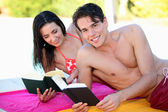 Couple reading books on the beach — Foto Stock