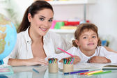 A female adult and a child girl drawing — Foto Stock