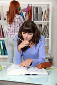 Two students in the library — Stock Photo