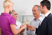 Men and women clinking glasses of champagne — Stock Photo