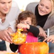 Young family carving hallowe'en pumpkins - Stock Photo
