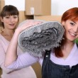 Stock Photo: Women moving a roll of carpet