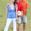 Three friends posing with a football — Stock Photo