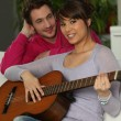 Young couple playing a guitar at home — 图库照片