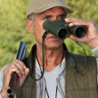 Hunter looking through binoculars - Stockfoto