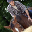 Young man riding a horse - Stock Photo