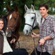 Young couple and horses in forest — Stock Photo #7800474
