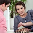 Young couple playing chess. — Stock Photo