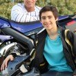 Stock Photo: Young men with a motorbike