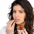 Woman eating strawberries — Stock Photo