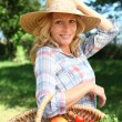 Womwith hand on her hat and basket of vegetables. — Stock Photo #7800600