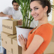 Couple moving plant into home — Stock Photo