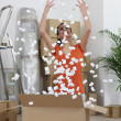 Woman excitedly throwing polystyrene peanuts in the air — Stock Photo