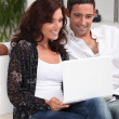 Couple with laptop in lounge — Stock Photo #7801503