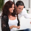 Stock Photo: Couple looking at photos on their laptop and reminiscing