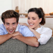 Young couple leaning on the back of their sofa — Stock Photo