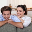 Young couple leaning on the back of their sofa — Foto de stock #7801941