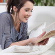 Woman reading a book on her sofa — Stock Photo #7801953
