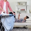 Man ironing while his girlfriend is reading a book on the couch - Zdjęcie stockowe