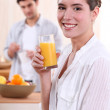 Woman drinking a glass of orange juice for breakfast — Stock Photo #7801976