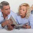 Couple looking at a catalogue — Stock Photo