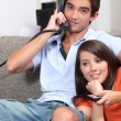 Stock Photo: Young couple relaxing on couch, talking on telephone and watching t