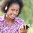 Beautiful black woman listening music in the park — Stock Photo