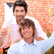 Homosexual couple in restaurant - Stock Photo