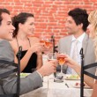 Friends raising their glasses in a toast at a restaurant — Stock Photo