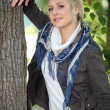 Fair-haired woman under tree - Stockfoto