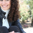 A curly-haired woman relaxing in a park — Stock Photo