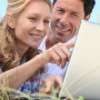 Stock Photo: Couple looking at laptop outdoors.
