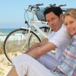 Stock Photo: Couple with bikes sitting on sand dunes