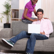 Casual couple using a laptop at home - Stock Photo