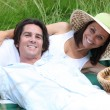 Couple lying on the grass with a basket of fruits — Stock Photo
