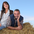 Farming couple sitting on a haystack - Stock Photo
