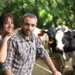 Farmer and his wife in front of their cows — Stock Photo #7802966