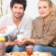 Couple eating breakfast on a sofa — Stock Photo